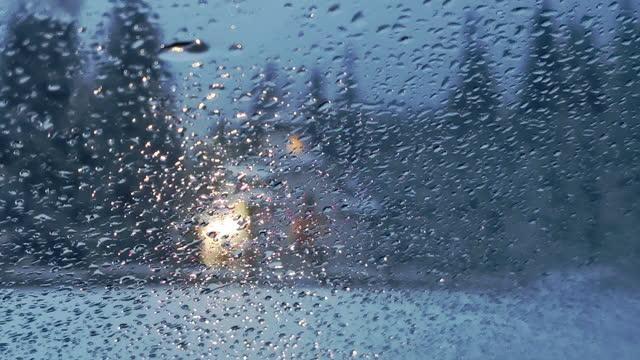 悪天候。小さな照らされた礼拝堂と外の冬の嵐で窓から見て。雪が降る突風。夕暮れ時に一生懸命雪が降る。 - 礼拝堂点の映像素材/bロール