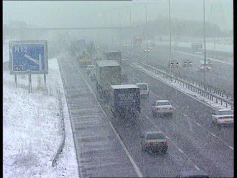bad weather roundup west yorkshire tbv slow traffic on motorway lams m62 motorway sign seen through snow tgv traffic along motorway in blizzard... - west yorkshire stock-videos und b-roll-filmmaterial