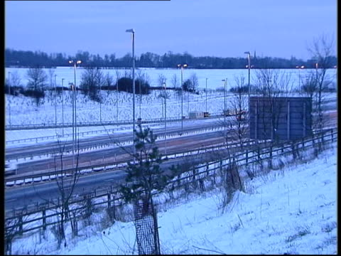 southern england itn traffic along road man pushing car along snowcovered road as wheels spinning in slush track air view lorries queueing in snow on... - slush stock videos and b-roll footage