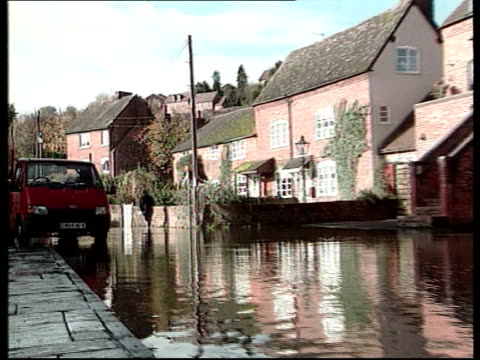 bad weather; west country: ext bv person along barefoot thru floodwater holding wellington boots floodwater rushing thru gateway as people along in... - skipton stock videos & royalty-free footage