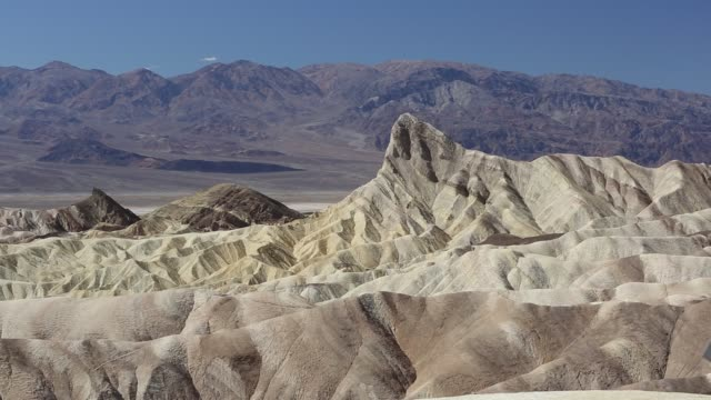 badland scenery at zabriskie point in death valley which is the lowest, hottest, driest place in the usa, with an average annual rainfall of around 2 inches, some years it does not receive any rain at all. - zabriskie point stock videos & royalty-free footage