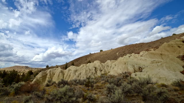 badlands yellow clay john day fossil beds formations clouds and shadows drift over a remote desert mountain sutton mountain close to the painted hills 13 - oregon us state stock videos & royalty-free footage