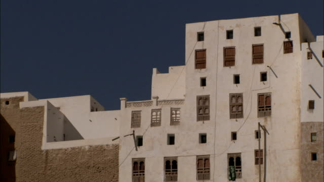 a badly damaged building stands before other high rise apartments. - yemen stock videos and b-roll footage