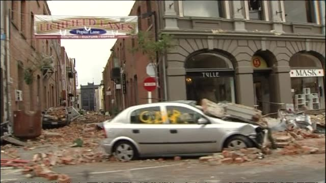 Badly damaged central city streets three days after second Christchurch earthquake with piles of masonry and bricks on crushed cars