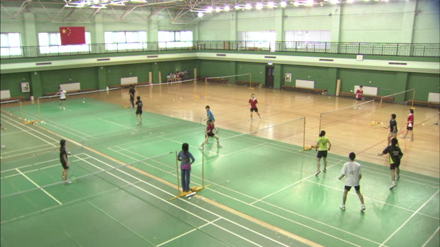 vidéos et rushes de badminton courts in gym w/ asian players, males & females practicing hitting shuttlecock, people's republic of china flag hanging above second floor... - badminton sport