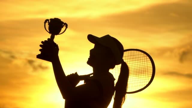 vídeos de stock, filmes e b-roll de um jogador de badminton comemora a vitória no jogo sunset silhueta - desempenho atlético