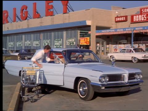 1962 bag boy loading groceries into car in front of grocery store / woman in car drives away