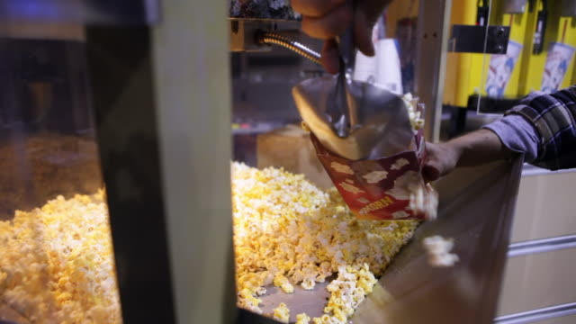 Bag of popcorn is filled in movie theater