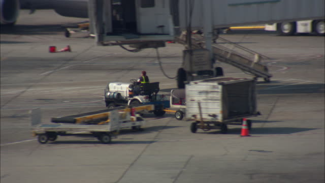 ws, ts, baggage cart riding on airport tarmac, los angeles international airport, los angeles, california, usa - luggage trolley stock videos & royalty-free footage