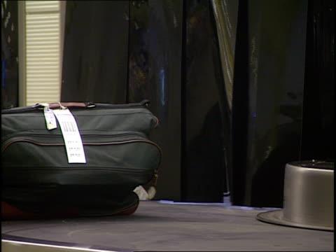 baggage circulates on a baggage claim conveyor belt. - ronald reagan washington national airport stock videos & royalty-free footage