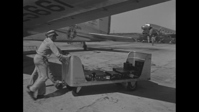 baggage handlers move a luggage trolley near a dc3's open cockpit door / men push a partially filled trolley to the airport terminal / men unload... - push cart stock videos and b-roll footage