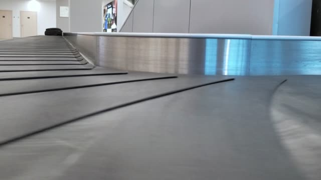 baggage is lost. the empty moving luggage carousel in the airport - diminishing perspective stock videos & royalty-free footage