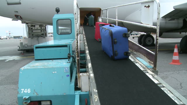 cu baggage loading in airplane  / airport luxembourg-findel, luxembourg - aereo militare video stock e b–roll