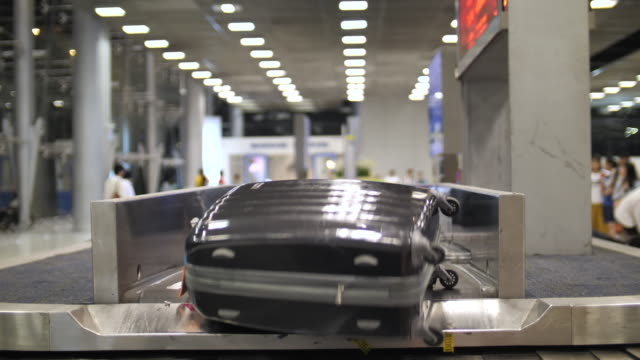 baggage on luggage carousel at airport - baggage claim stock videos and b-roll footage