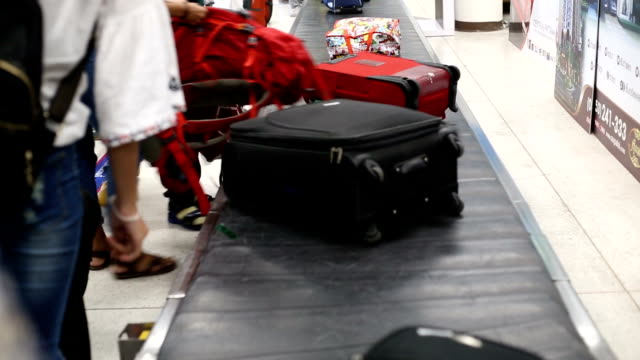Baggage on the belt conveyor ,people wait for load  luggage