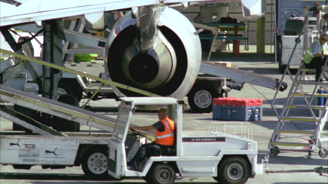 ms, baggage transport truck pulling up at aircraft on tarmac, los angeles, california, usa - luggage stock videos & royalty-free footage