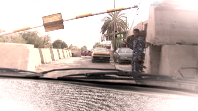 vídeos de stock e filmes b-roll de sadr city: ext graphicised reconstruction seq road seen from driver point of view then checkpoint barrier opening / people at stalls in marketplace /... - cross legged