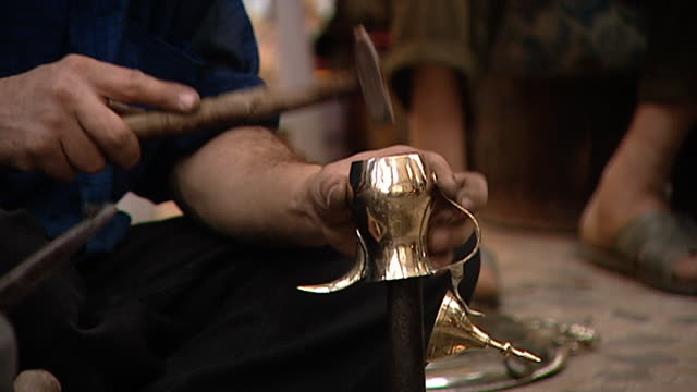 baghdad before the 2003 gulf war a busy scene in souq al safafir cu shot of a coppersmith in front of his stall hammering a shiny new copper coffee... - coffee pot stock videos & royalty-free footage