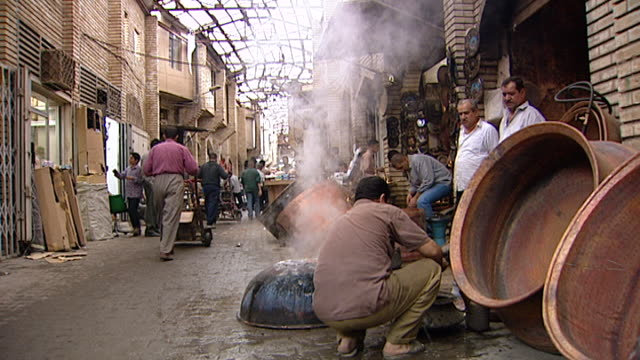 baghdad before the 2003 gulf war. a busy scene in souq al safafir showing stalls, vendors, shoppers and tradesmen. a man is pouring water over a hot... - bricco per il caffè video stock e b–roll
