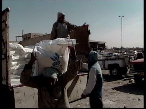 baghdad ext la aid workers moving sacks of un supplies cms two sacks of handout rations on ground as picked up cms old iraqi woman wearing black... - headdress stock videos and b-roll footage