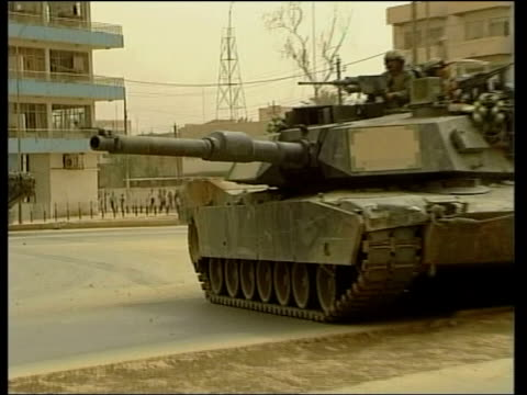 baghdad iraqi citizens celebrating fall of saddam hussein's regime pull out us tank us soldiers on turret of tank soldier crouched on ground with... - バグダッド点の映像素材/bロール