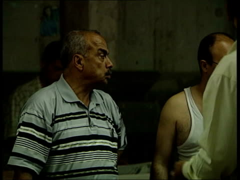 baghdad ext iraqi men looking wary adib shaaban listening against door then pressing doorbell bodyguards standing around man out of newspaper... - worry beads stock videos & royalty-free footage