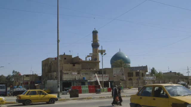 baghdad street, mosque in background, wide shot - minareto video stock e b–roll