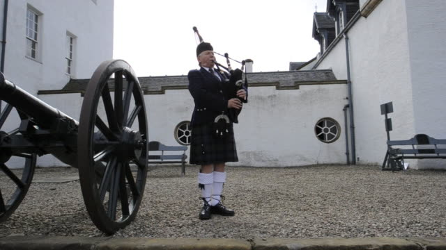Bagpiper Gillie McNab performs near cannons at Blair Castle.