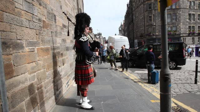 bagpiper on the royal mile in edinburghs old town playing for tourists. - タータンチェック点の映像素材/bロール