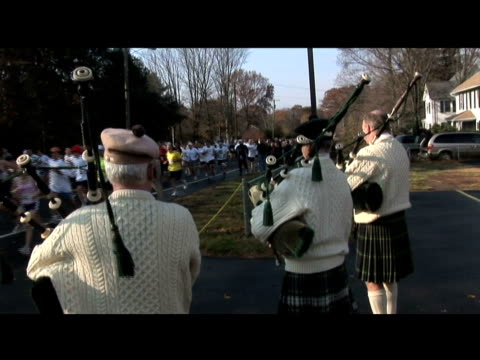 bagpipers with a mass of runners in background bagpipers playing with runners on january 01 2012 - salmini stock videos & royalty-free footage