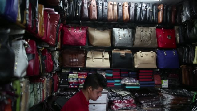 vídeos y material grabado en eventos de stock de bags are displayed in the window of a leather goods store in the dharavi area of mumbai, india, on tuesday, july 18 a vendor uses a mobile phone... - iva