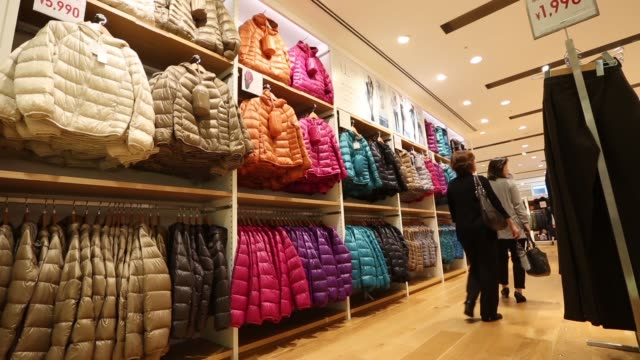 vídeos y material grabado en eventos de stock de bags containing ultra light down jackets are displayed for sale in a uniqlo store, operated by fast retailing co., in the ginza district of tokyo,... - camisola