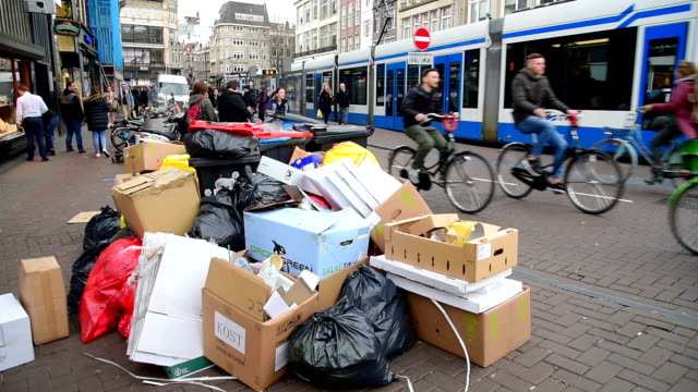 bags of rubbish and garbage along a central street and canal in amsterdam - bin bag stock videos & royalty-free footage