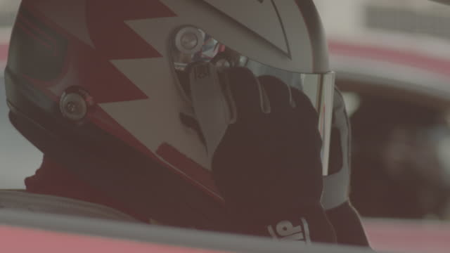 bahrain international circuit. view of two racing drivers with their helmets on sitting inside their sports cars on the race track. the first grand... - formula one racing stock videos & royalty-free footage