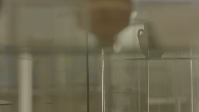 bahrain national museum. track-left to a pot and a jug from the dilmun era displayed at the museum. a bahraini woman is looking at the display. - wine glass stock videos & royalty-free footage