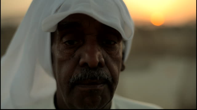 bahrain portrait cu portrait of a bahraini man in a traditional white keffiyeh and thobe shot against an orange sunset - dish dash stock videos & royalty-free footage