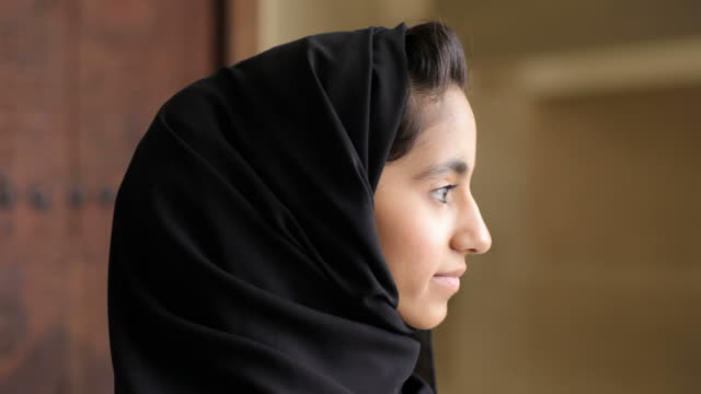 bahrain portrait. portrait of a young woman in traditional hijab turning from profile to face the camera with a small diffident smile on her face. - profile stock videos & royalty-free footage