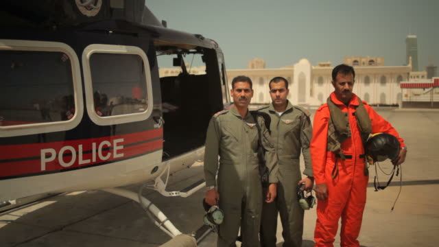 bahrain portrait. view of three bahraini police pilots posing next to their helicopter. - ヘリポート点の映像素材/bロール