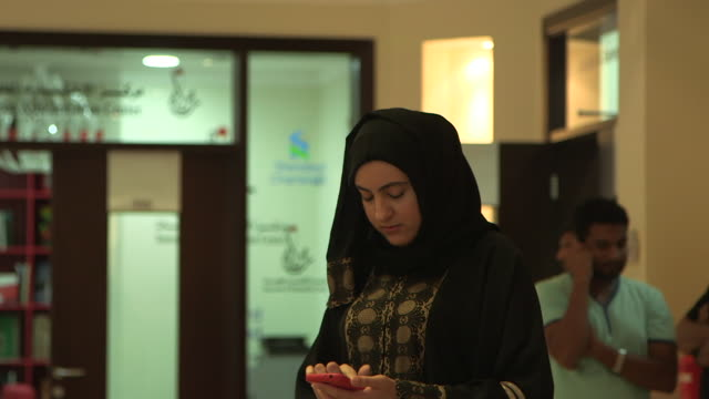 bahraini woman looking at her mobile phone. - handheld stock videos & royalty-free footage