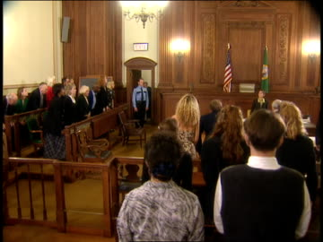 a bailiff announces a judge's entrance into a courtroom, jury and spectators rise as the judge enters, then sit down again. - legal trial stock videos & royalty-free footage