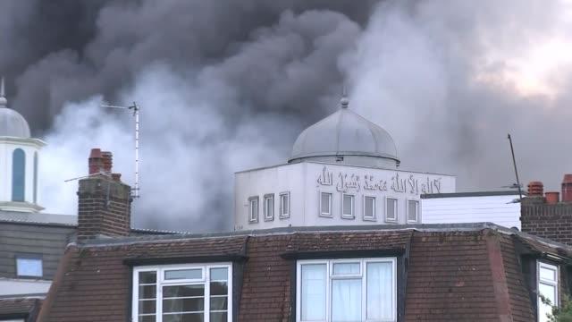 two teenagers arrested on suspicion of arson england london morden ext smoke rising from baitul futuh mosque on fire various shots firedamaged mosque - moské bildbanksvideor och videomaterial från bakom kulisserna