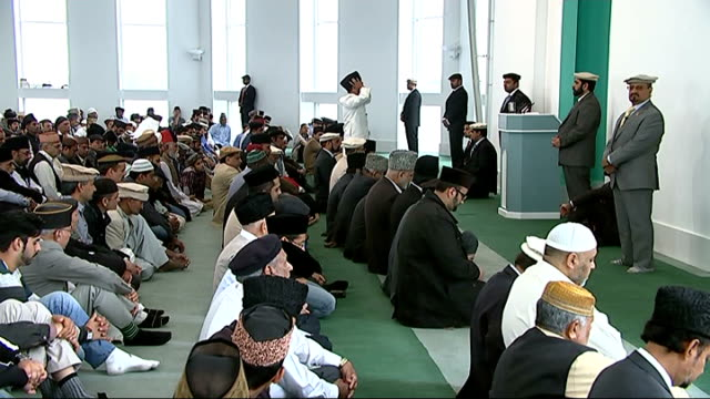 His Holiness Mirza Masroor Ahmad interview ENGLAND London Morden INT Muslims seated in mosque / His Holiness Mirza Masroor Ahmad along into room with...