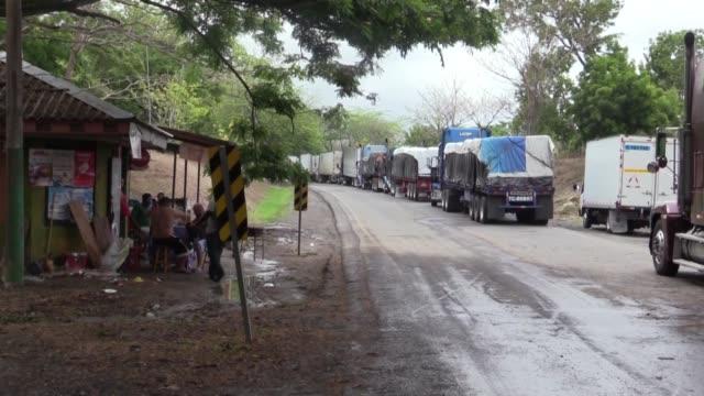 bajo sol y lluvia, mal alimentados y comprando agua para beber o bañarse, los camioneros de carga centroamericanos han pasado días en la frontera... - transporte stock videos & royalty-free footage