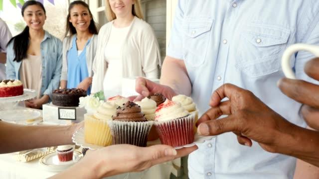 vídeos y material grabado en eventos de stock de cuece al horno venta voluntaria sirve cupcakes para los huéspedes - anfitriona de la fiesta