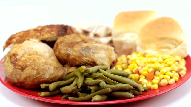 Baked chicken plated with vegetables and rolls. Left rotating. Wide Shot.