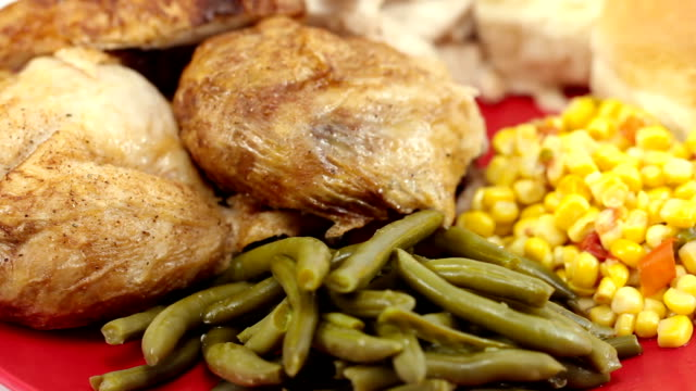 baked chicken plated with vegetables and rolls. rotating right. tight shot. - green bean stock videos & royalty-free footage