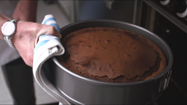 baked flourless dark chocolate cake recipe being removed from oven. - oven stock videos & royalty-free footage