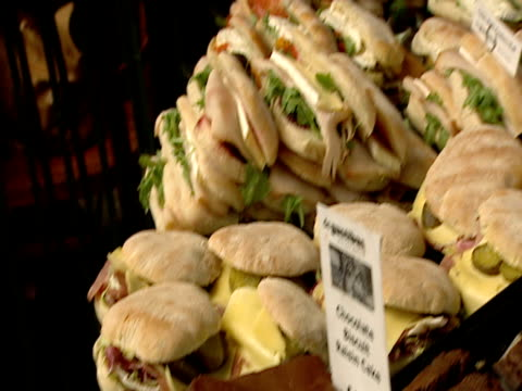 baked goods and largesandwiches on display at market stall - おやつ点の映像素材/bロール