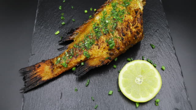 baked grouper fish isolated on black background with lemon and shallot - shallot stock videos & royalty-free footage