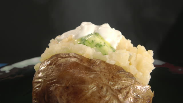 cu baked potato with sour cream and melting herb butter as chives are sprinkled on top - sprinkling stock videos and b-roll footage